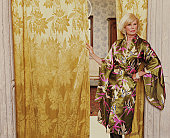 Mature woman standing by curtained doorway, hand on hip, portrait