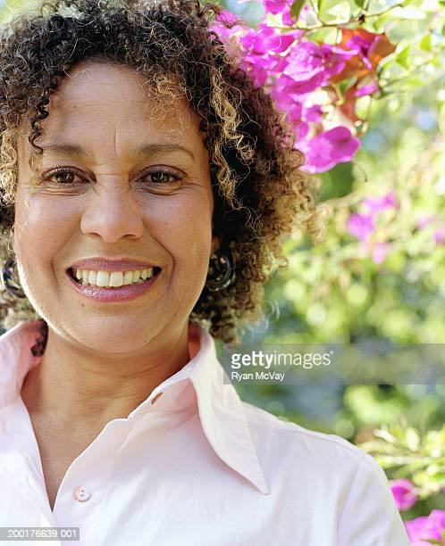 Mature woman standing by flowers, smiling, portrait