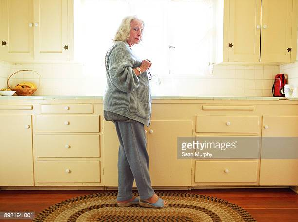 Mature woman standing by kitchen sink holding glasses
