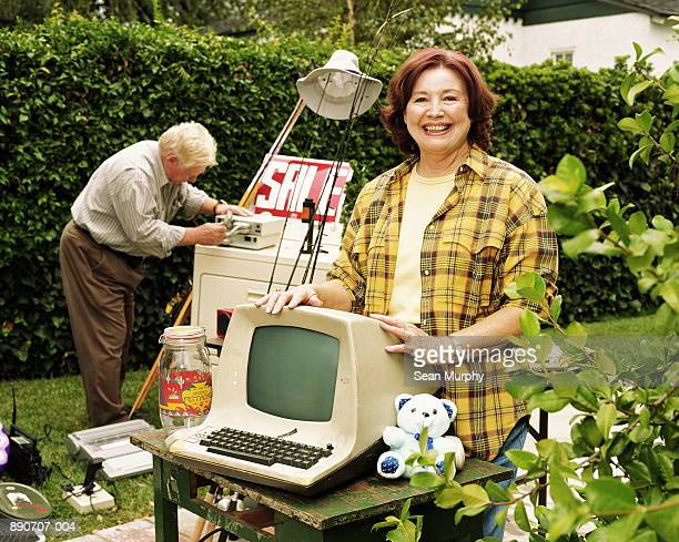 Mature woman standing by old computer monitor at yard sale