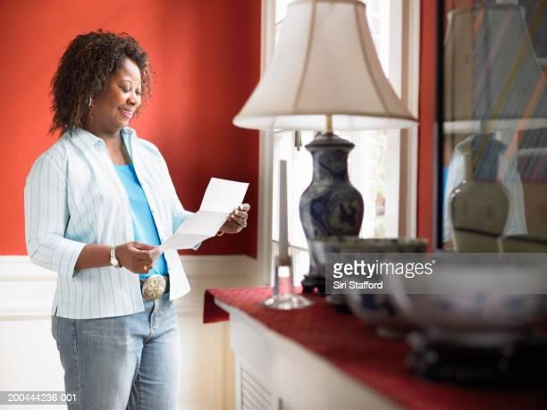 Reife Frau stehend durch Fenster Lesung mail