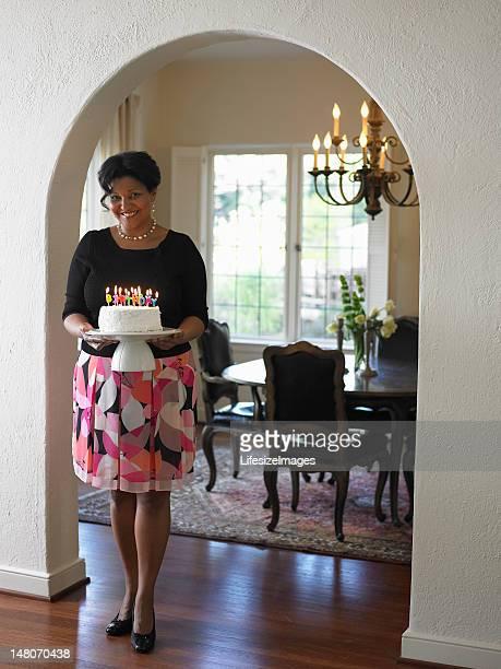 Mature woman standing in doorway, holding birthday cake, portrai