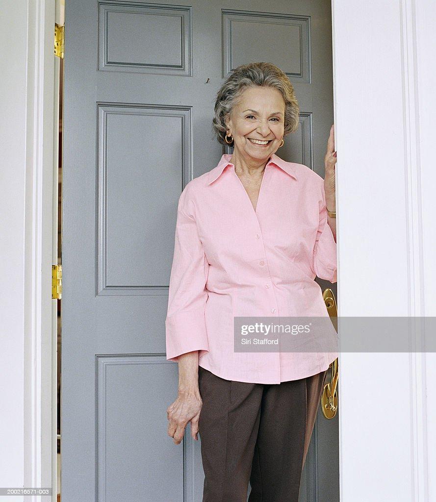 Mature woman standing in doorway, portrait : Stock Photo
