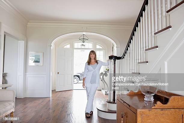 Mature woman standing in entrance hall of home