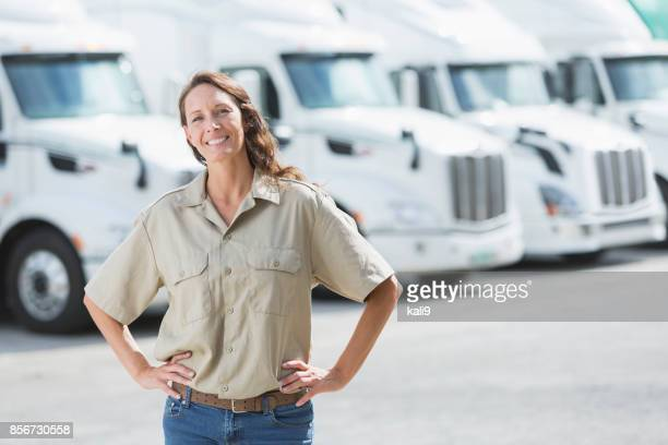 Mature woman standing in front of semi-trucks