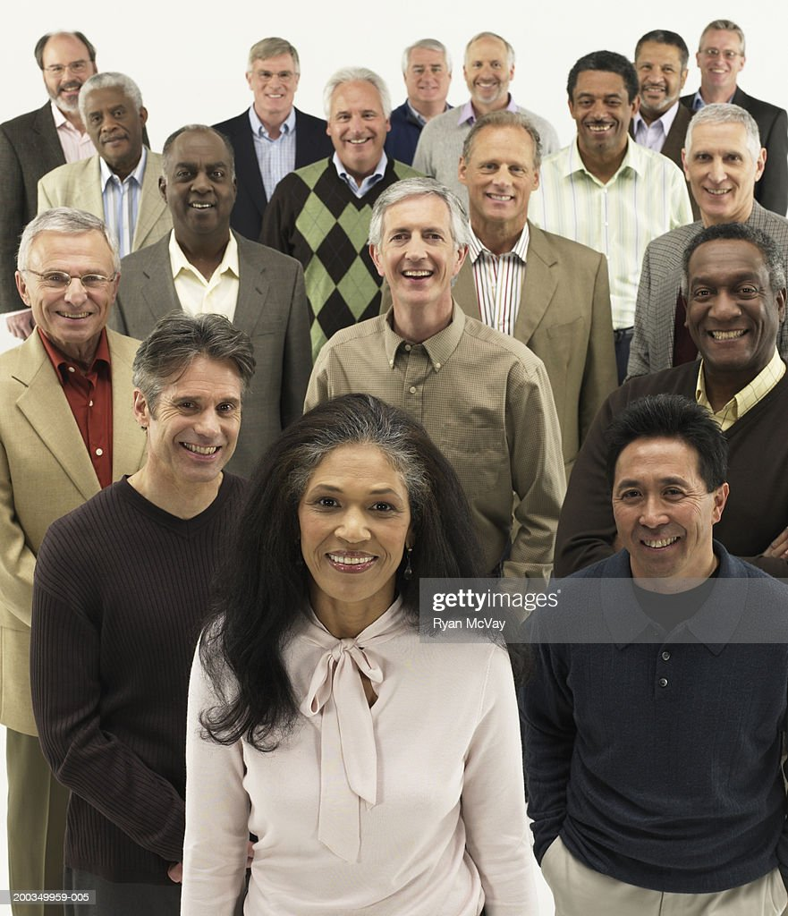 Mature woman standing in group of mature men, smiling, portrait