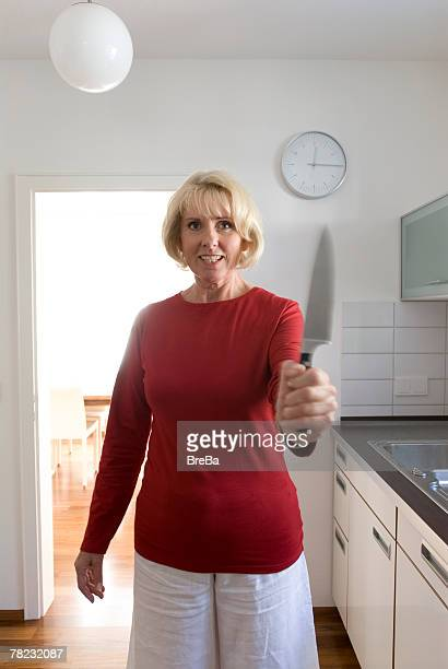 mature woman standing in kitchen holding knife