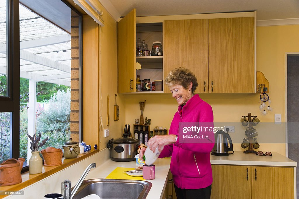 Mature woman standing in kitchen : Stock Photo