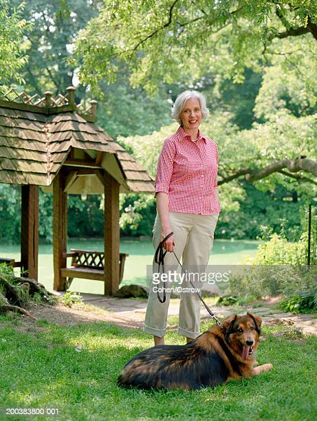 Mature woman standing in park with dog on leash, smiling, portrait