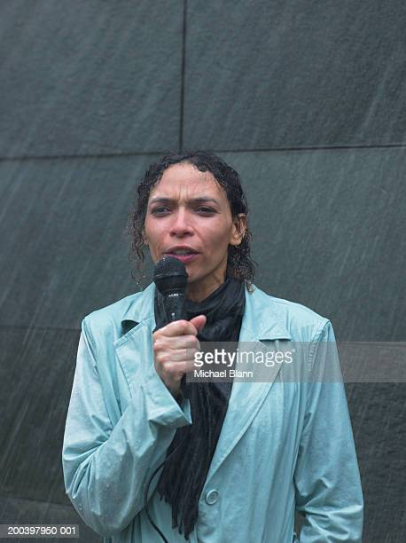 Mature woman standing in rain holding microphone, close-up