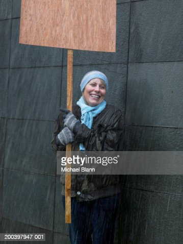 Mature woman standing in rain holding placard, looking away, laughing