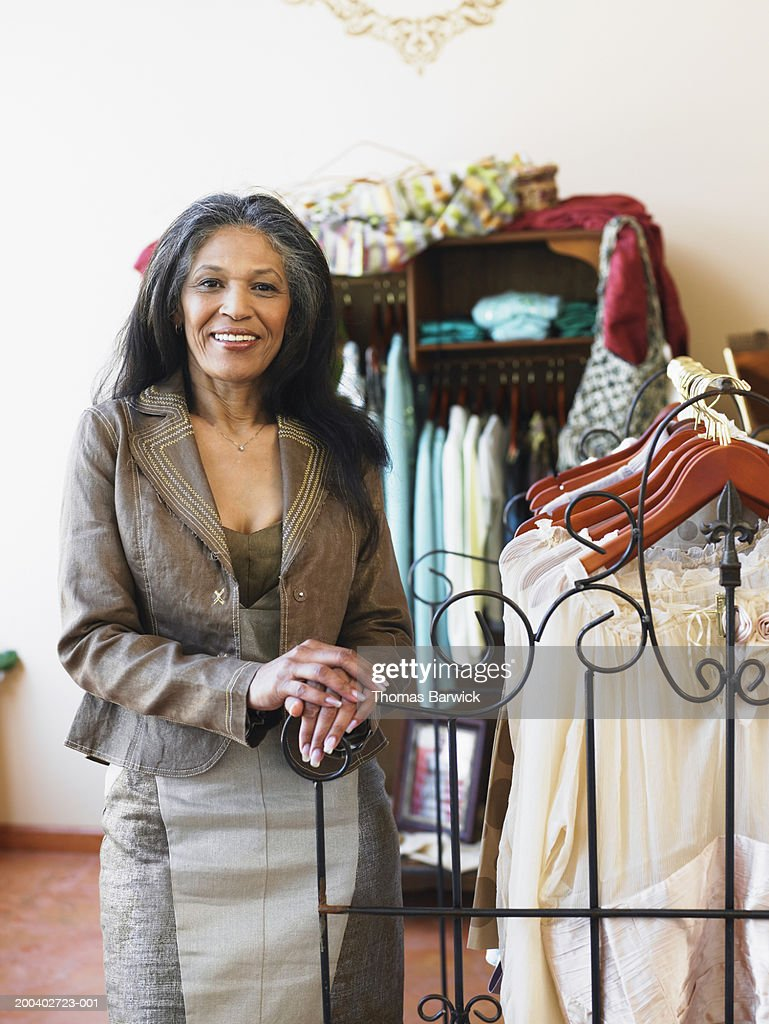 Mature woman standing in retail clothing store, smiling, portrait : Stock Photo