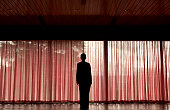 Mature woman standing in silhouette against red curtains
