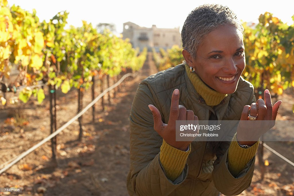 Mature woman standing in vineyard, making hand gestures, smiling