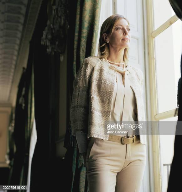 Mature femme debout à l'intérieur, regardant par la fenêtre, gros plan
