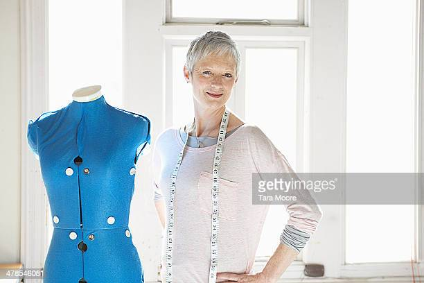 mature woman standing next to dress form