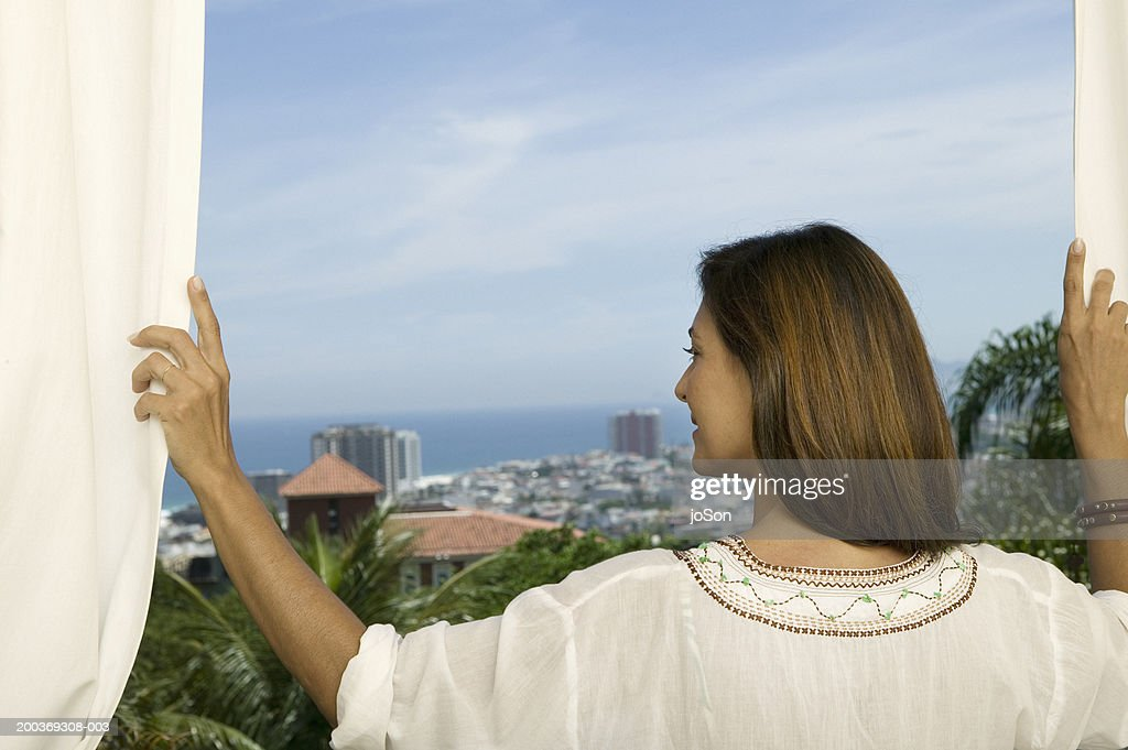 Mature woman standing on balcony overlooking ocean rear for Balcony overlooking ocean