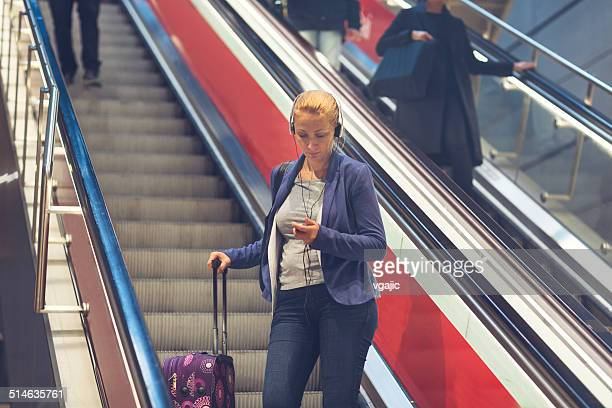 Mature Woman Standing on Escalaltor With Luggage.
