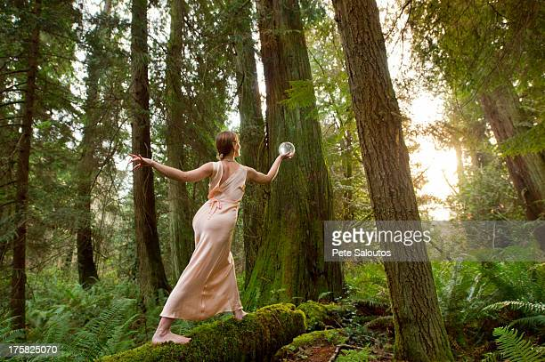 Mature woman standing on log in forest