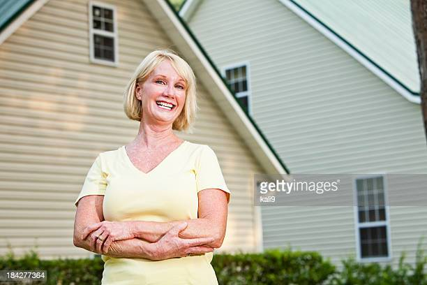 Mature woman standing outside home
