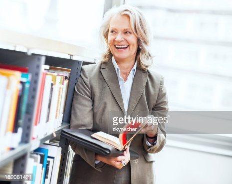 Mature woman standing with book in her hand.