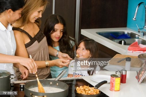 Mature woman standing with her two daughters and a maid smiling in the kitchen : Stock Photo