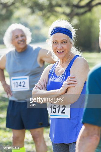 Mature woman  standing with other runners after race : Stock Photo