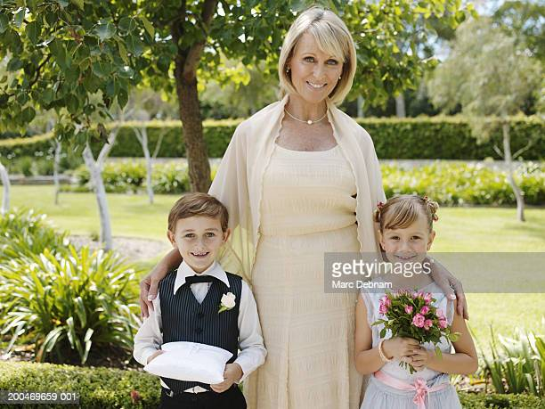 Mature woman standing with page boy and bridesmaid (6-7)