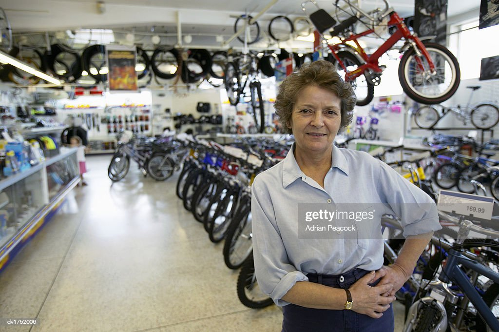 Mature Woman Stands in a Bicycle Shop With Her Hands on Her Hip : Stock Photo