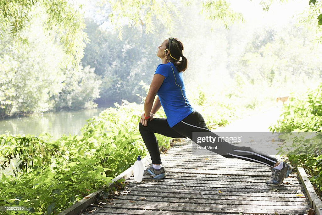 A mature woman stretching before a run : Stock Photo