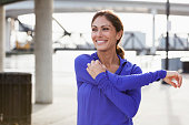 Mature woman taking a break from running to stretch her arms, looking at the view on the waterfront.