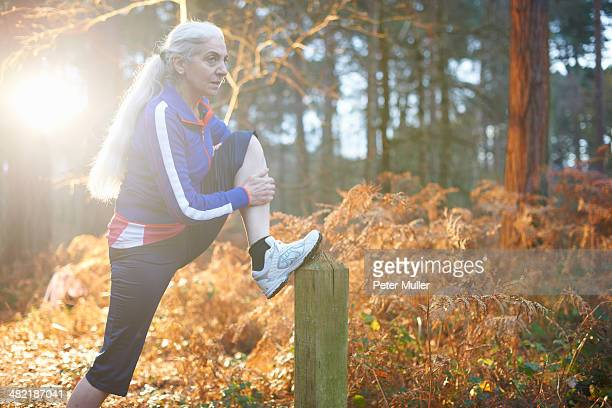 Mature woman stretching leg on wooden post