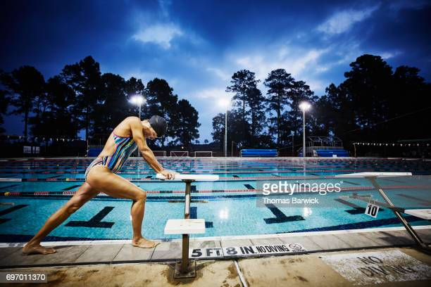 Mature woman stretching on deck of outdoor pool before early morning workout