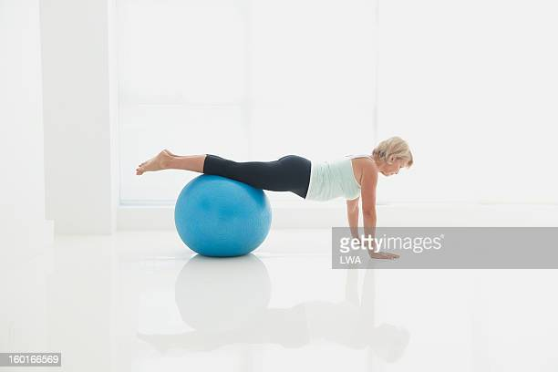 Mature woman stretching on exercise ball