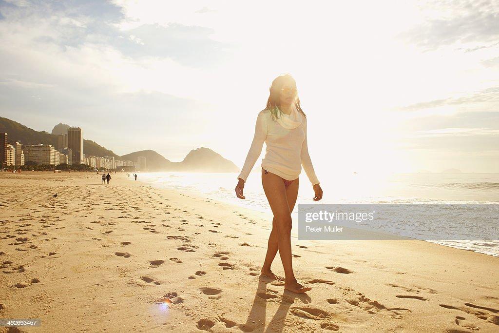 Mature woman strolling on sunlit Copacabana beach, Rio De Janeiro, Brazil