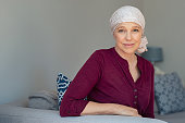 Mature woman with cancer in pink headscarf smiling sitting on couch at home. Smiling woman suffering from cancer sitting after taking chemotherapy sessions. Portrait of mature lady facing side-effects