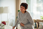Mature woman suffering from stomach ache at home. Grabbing and squeezing belly with hand, feeling exhausted, standing in living room. Expressing pain on face