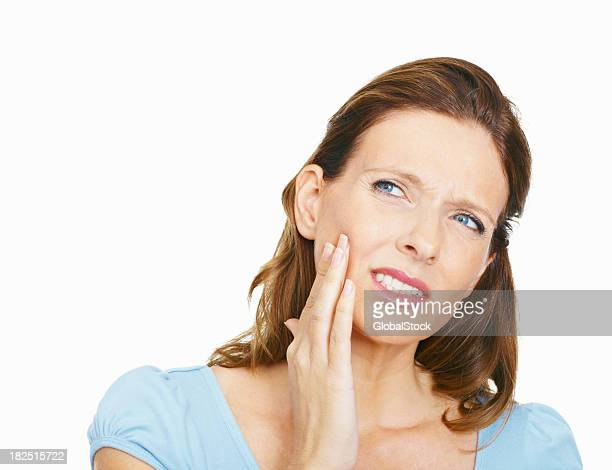 Mature woman suffering from toothache on white background