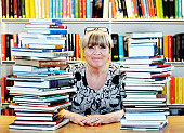 Mature woman surrounded by books in library