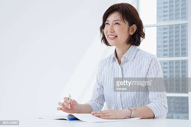 Mature woman taking a note, smiling