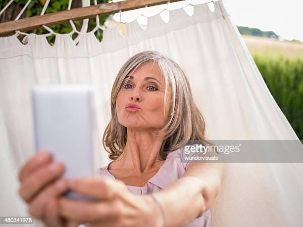 Reife Frau nimmt ein Selbstporträt mit Ihrem küssen Gesicht