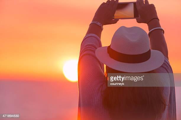 Donna matura che telefono cellulare Foto al tramonto.