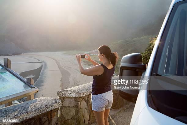 Mature woman taking photo of coastal landscape