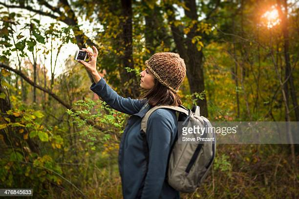 Mature woman taking photograph in forest using smartphone