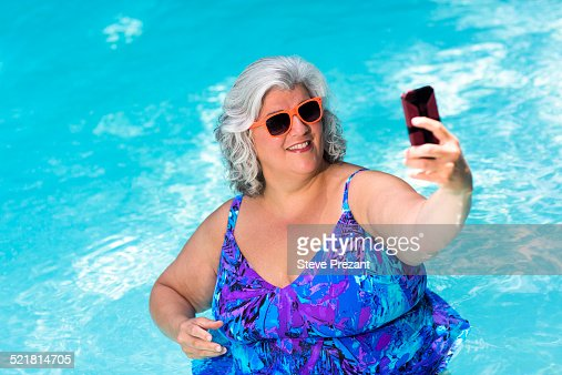 Mature woman taking selfie on smartphone at poolside