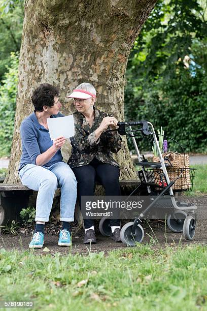 Mature woman talking to senior woman with wheeled walker on park bench