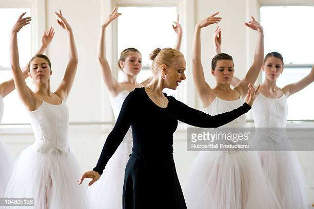 Mature woman teaching girls (12-13,14-15,16-17) ballet in studio