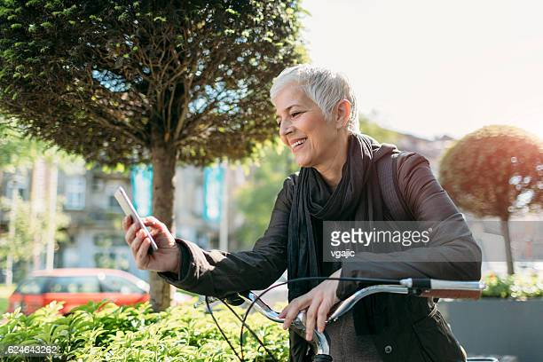 Mature Woman Texting On Her Smart Phone Outdoors