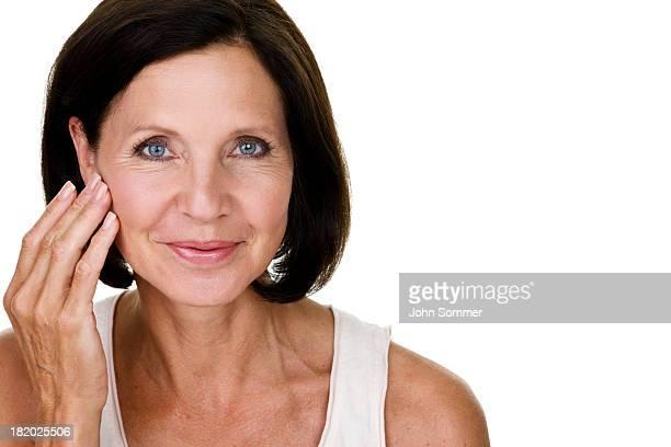 Mujer madura tocando su rostro