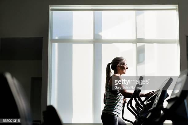 Mature woman training on gym machine